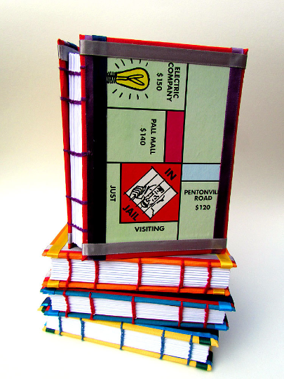 Coptic stitched handmade notebooks using repurposed Monopoly boards for covers.